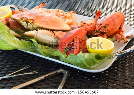 Red lobster, dungeness crab and jumbo Shrimps on a plate along with sea sheller utensils - stock photo