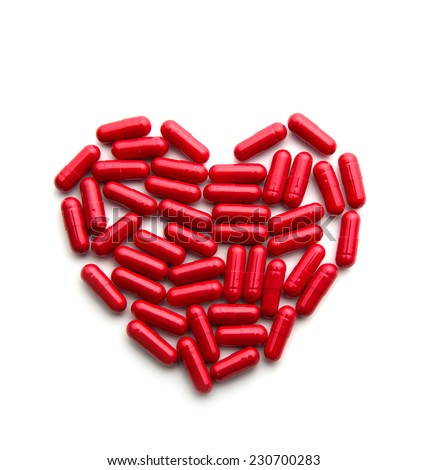 Red long pills in a heart form - stock photo