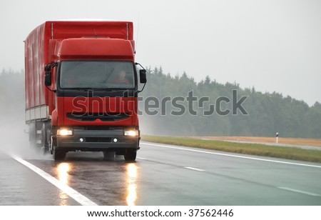 Red lorry with red trailer at wet road during the rain. Find more vans and trucks in my portfolio - stock photo