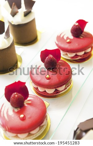 Red macaroons with berries on top - stock photo