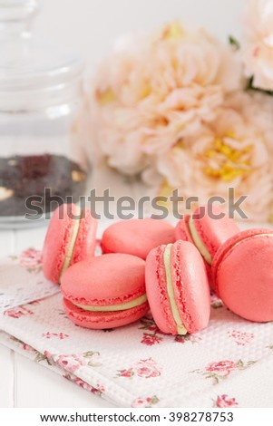 Red macaroons with green cream ganache on pastel background with flowers. Romantic french pastry for valentines day. Shallow focus - stock photo