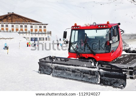 Red machine for skiing slope preparations in Austrian Alps, building and tourists. - stock photo