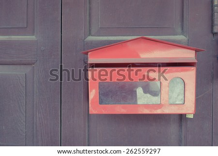 red mailbox on old door background (vintage style) - stock photo