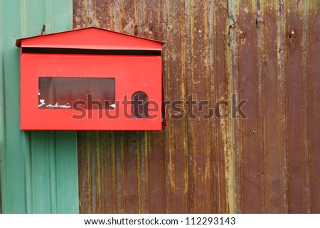 Red mailbox on rusty iron fence - stock photo