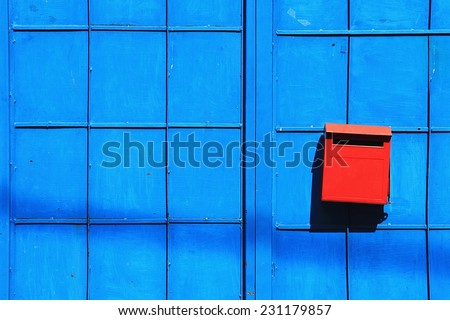 Red mailbox on the blue door. Red postbox on blue blackground. - stock photo