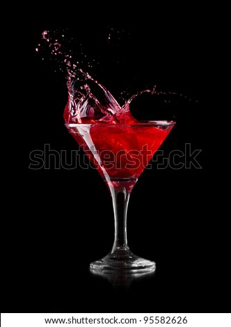red martini cocktail splashing into glass on black background - stock photo
