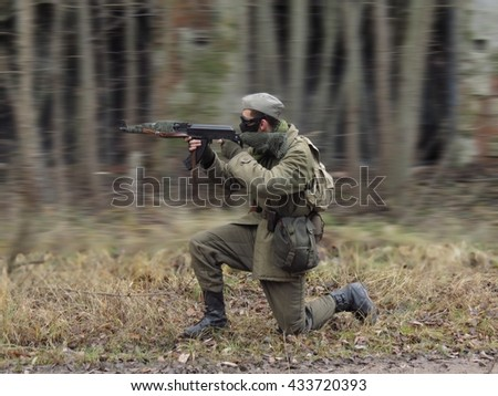 Red Masked airsoft player, who plays for Russian side of the army, old time scenery, motion blur blackground - stock photo