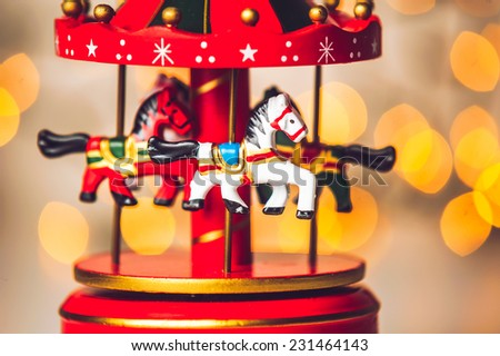 Red merry-go-round horse carillon, wooden carouse against blurred background, christmas decoration - stock photo