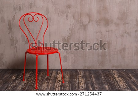 Red metal chair in nterior room with gray decorative plaster wall and dark wooden floor - stock photo