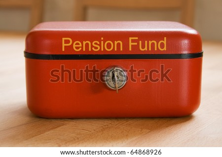 Red metal pension fund savings tin on a wooden surface - stock photo