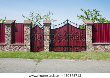 Red Metal Profil Gate with Decorative Gate and Door in Old Stiletto against Blue Sky - stock photo