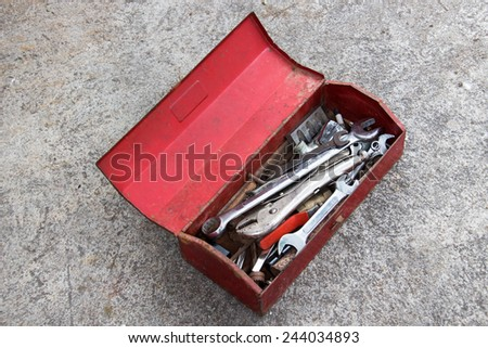 Red Metal Tool Box on Concrete Floor - stock photo