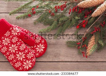 red mitten, fir and berry on old wooden background - stock photo