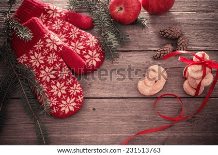red mittens and christmas decoration on wooden background - stock photo