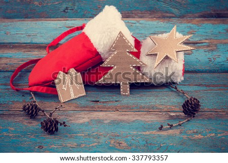Red mittens with fur and a branch of pine tree with cones on painted blue wooden boards. Christmas and New Year. - stock photo