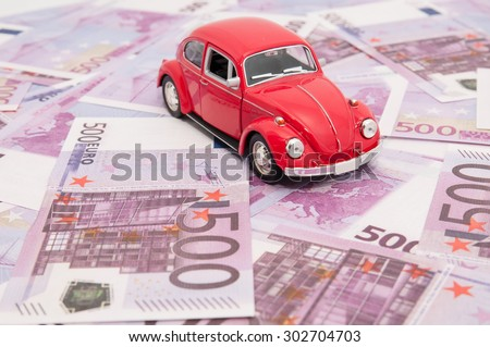 Red model car on banknotes, symbolic photo for car buying,  - stock photo