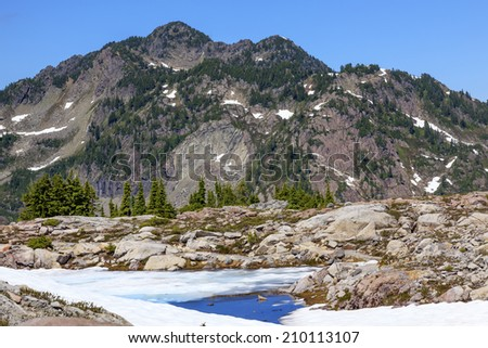 Red Mountains Small Blue Snow Pond Artist Point Mount Baker Highway in July Summertime - stock photo