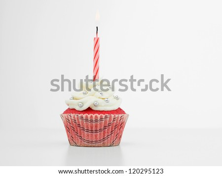 red muffin with cream  white and candy silve one red spiral burning candle on white background isolated - stock photo