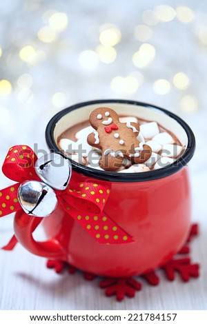 Red mugs with hot chocolate, marshmallows and gingerbread man - stock photo