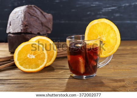 red mulled wine with fruits, cinnamon sticks with big piece of black chocolate on background on a wooden table  - stock photo
