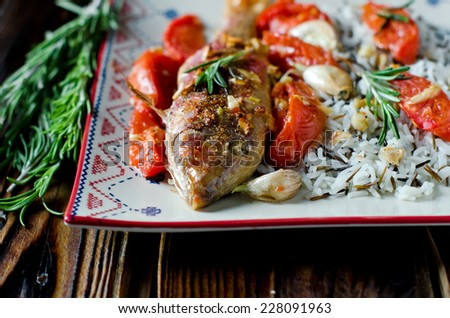 Red mullet baked with tomato, garlic and rosemary with a garnish of rice - stock photo
