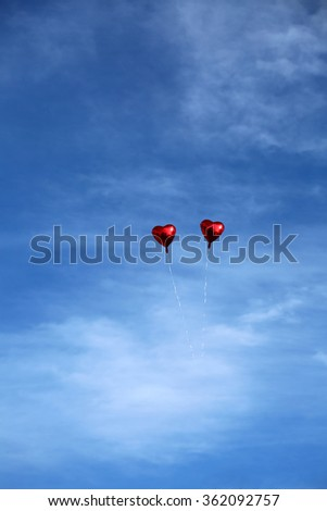 Red Mylar Heart Shaped Valentines Day Helium Filled Balloon floats freely into the Blue Sky with White Clouds. Valentines Day is celebrated on February 14 of each year. - stock photo