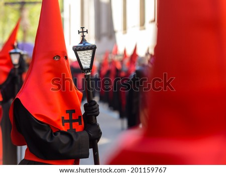 Red nazareno with a lamp in the Good Thursday during Holy Week in Valladolid. - stock photo