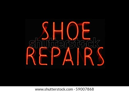 Red neon sign of the words 'Shoe repairs' on a black background. - stock photo