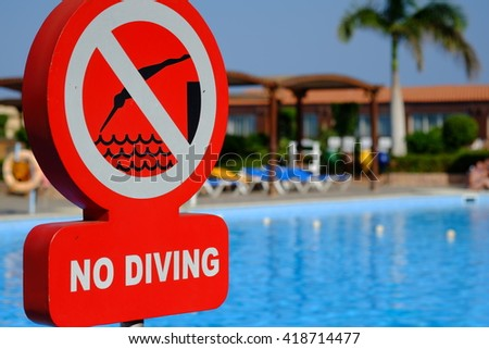 Red no diving warning sign at the poolside - stock photo