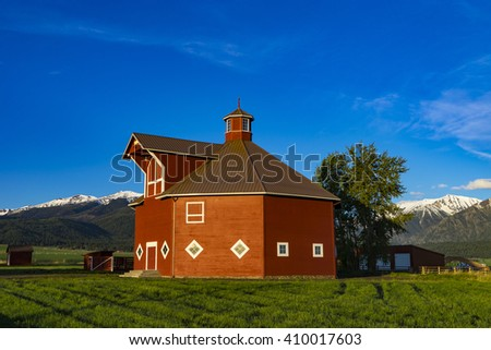 Red octagonal barn near the Wallowa Mountains in Oregon - stock photo