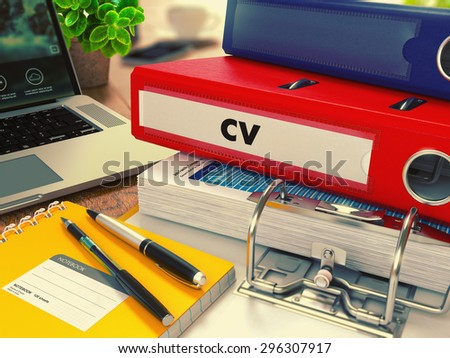 Red Office Folder with Inscription CV - Curriculum Vitae - on Office Desktop with Office Supplies and Modern Laptop. Business Concept on Blurred Background. Toned Image. - stock photo