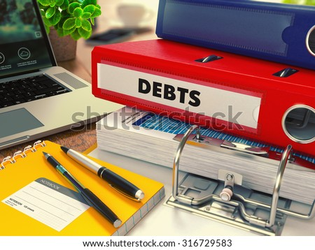 Red Office Folder with Inscription Debts on Office Desktop with Office Supplies and Modern Laptop. Business Concept on Blurred Background. Toned Image. - stock photo