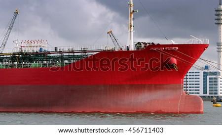 Red Oil Tanker. Oil Tanker Docked at Port of Rotterdam. Large oil tanker in port.  Petroleum shipping pier. Crude oil tanker is loading in port. - stock photo