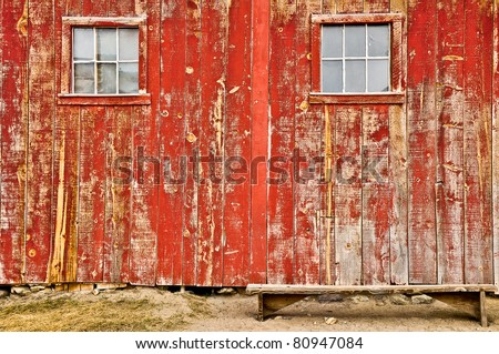 Red old barn with two windows and lonely bench, no sky and no horizon - stock photo
