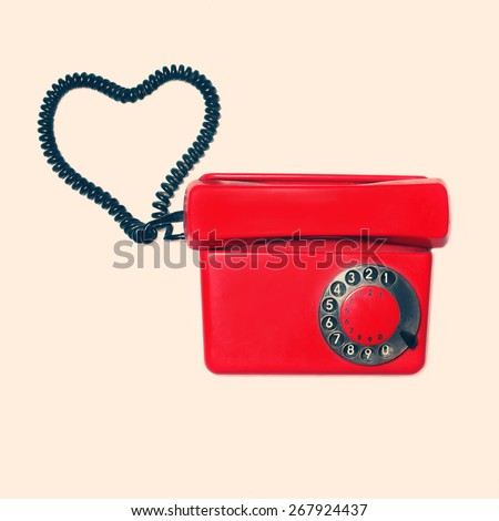 Red old retro rotary phone with heart shape of wire, vintage colors photo - stock photo