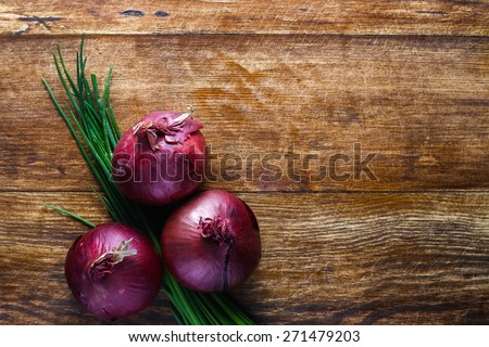 Red onions and bunch chives composition lying on the wooden table - stock photo