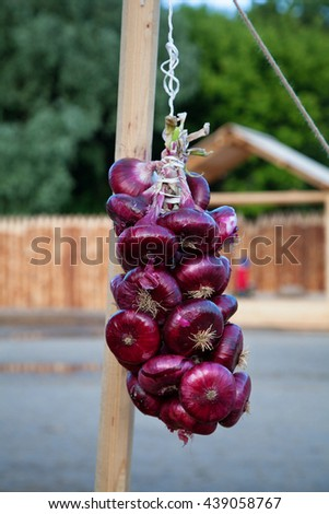 red onions on a rope, village market - stock photo