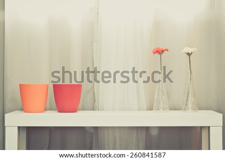 red, orange pots & red, yellow flowers in glass vase on white table on soft color curtain background + art filter - stock photo
