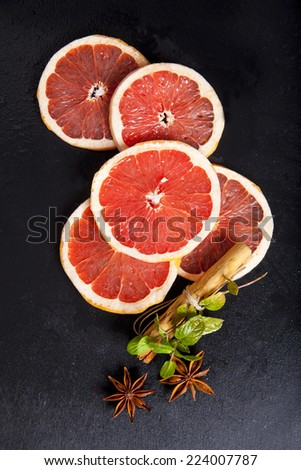 Red orange with cloves, cinnamon, mint & star anis on dark. still life. christmas decoration. ingredient for hot winter drink  - stock photo