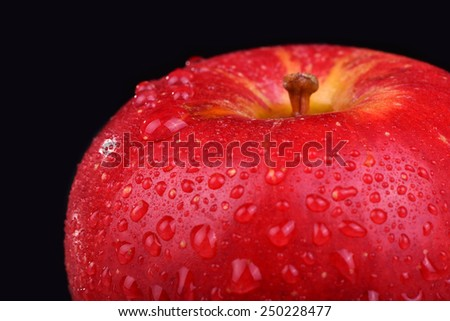 Red organic apple with water drops on a black background. Macro water drops - stock photo