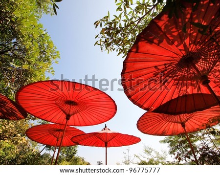 Red oriental bamboo umbrellas with leaf shadow under the sun - stock photo