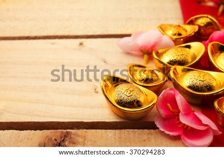 "Red packet , Shoe-shaped gold ingot (Yuan Bao with Chinese character ""Fu"" means fortune on top) and Plum Flowers over wooden background with copy space - best for Chinese New Year use - stock photo"