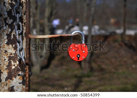 Red padlock hanging on a rusty bar. - stock photo