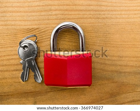 Red padlock with keys on wooden background - stock photo