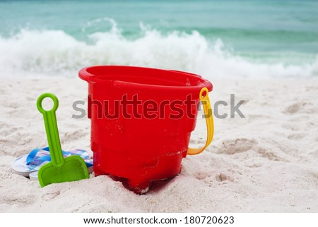 Red pail and shovel with flippers on ocean beach - stock photo