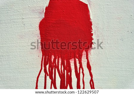 Red paint drips over textured white wall. Abstract background. - stock photo