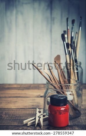 Red paint with art and craft tools on wooden background. Toned. - stock photo