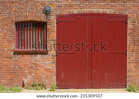 Red painted wooden barn door and window with bars in old brick wall to quayside building at Dell Quay in Chichester Harbour. West Sussex. England - stock photo