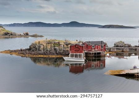 Red painted wooden fishing shacks at New Foundland, NL, Canada, Atlantic Ocean coast calm cove - stock photo