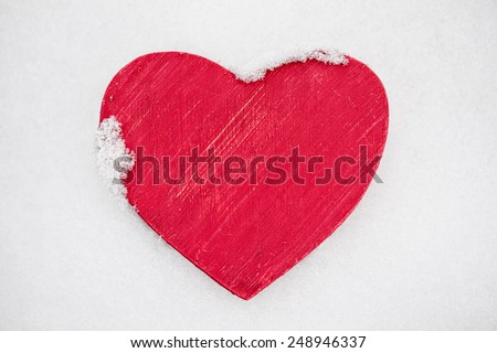 Red painted wooden heart covered in real fresh snow in winter for Valentines Day - stock photo